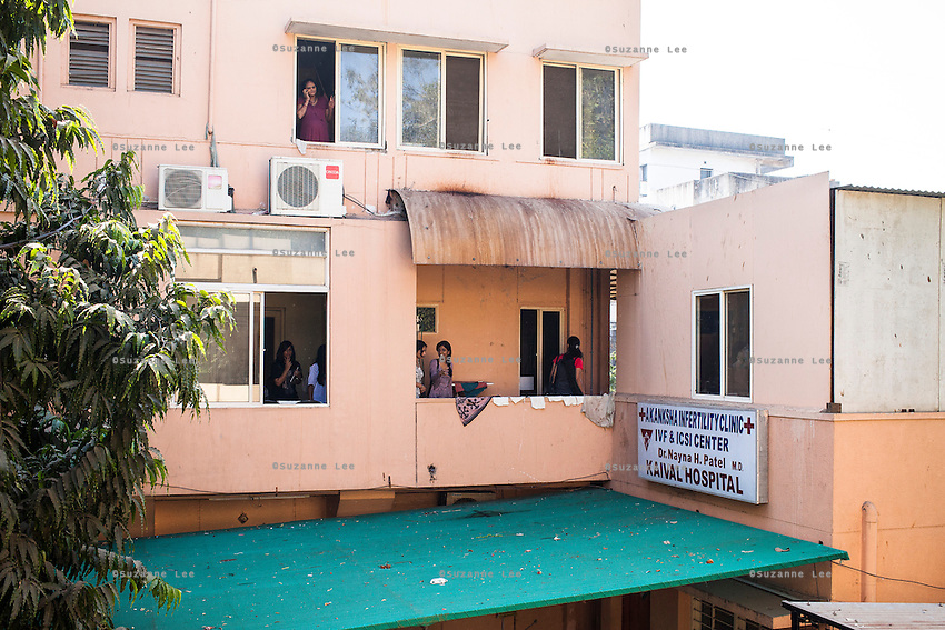 A group of women walk around on the 1st floor as a surrogate looks out the window while talking on her mobile phone in the surrogates floor of the Akanksha Clinic in Anand, Gujarat, India on 12th December 2012. Photo by Suzanne Lee / Marie-Claire France