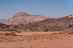 Desert sand and mountains in the Wadi Rum Protected Area, a UNESCO World Heritage Site.  Um Sahn sandstone with Rum sandstone behind  A tent camp is situated at the base of the wall.  Hashemite Kingdom of Jordan.