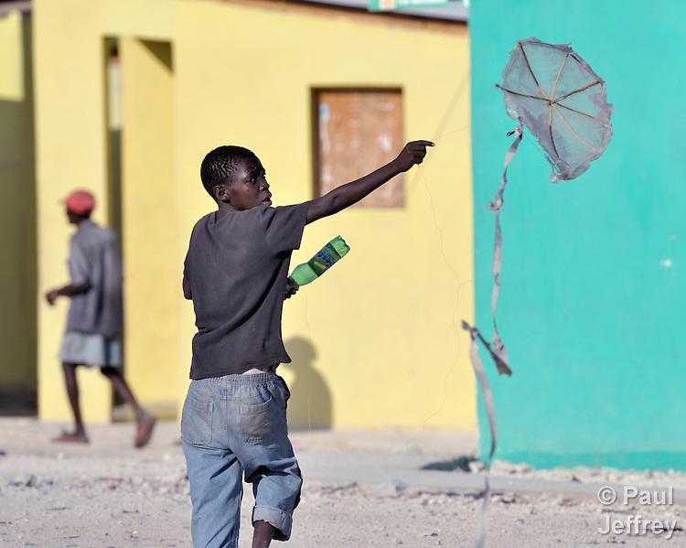 A boy launches a kite in Cite Soleil, a sprawling poor portion of Port-au-Prince, Haiti. Behind him is new homes for earthquake victims, constructed by an italian nun working in the neighborhood.