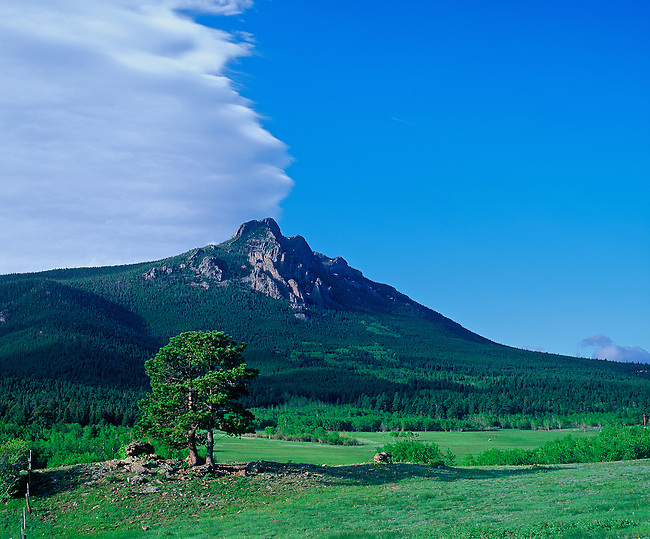 Lenticular clouds, caused by high altitude winds, hover over the Crags on Twin Sisters Mountain, near Estes Park, Colorado, USA