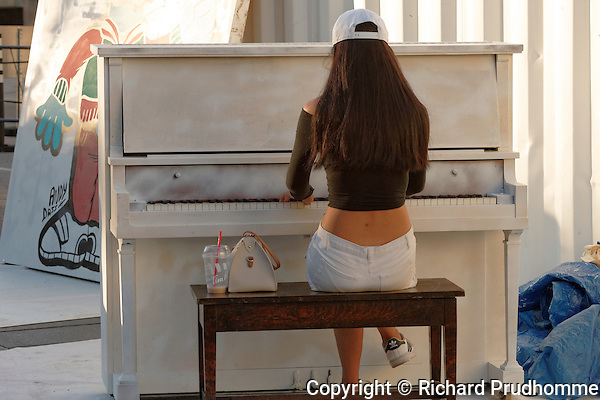 A young woman playing the outdoor piano at the Fashion and Design Festival in downtown Montreal, Quebec.