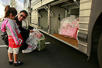 A San Diego Police Officer helps a young girl load her purchases onto the bus that will take her home after the Shop-With-a-Cop event at the Sports Arena Target store in San Diego on December 1, 2007.  Some children rose well before dawn in order to be ready for the fleet of buses that collected them from every corner of the county and took them to SeaWorld where they were paired up with an officer for the event.  After breakfast they made their way to the Target store in a huge, convoy of more than three hundred police vehicles with sirens blaring, lights flashing and Santa waving from a police helicopter hovering above them.  Each child had a $100 gift card to spend and many of them resisted the temptation to buy toys and choose instead to get clothes for themselves, their siblings or parents.