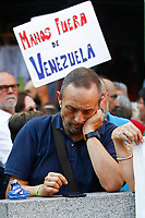 "Demonstrators  supports President Maduro holds a poster entitle ""Hands out of Venezuela""."