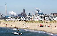 Nederland IJmuiden 2016. Strandhuisjes in IJmuiden. Op de achtergrond Tata Steel, de vroegere hoogovens. Foto Berlinda van Dam / Hollandse Hoogte