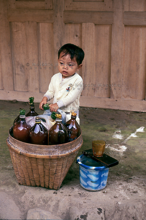 Indonesia, Java island, a child near bottles of jamu (traditional Javanese herbal medicine).<br />