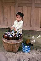 Indonesia, Java island, a child near bottles of jamu (traditional Javanese herbal medicine).<br /> Indonesia; Giava, bambino vicino contenitori di jamu ( medicina tradizionale giavanese)