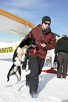 Dropped dog handler Morgan Peters takes a dropped dog from an airplane Thursday to his resting place in McGrath