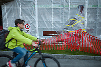 Switzerland. Canton Ticino. Lugano. A young boy rides his bicycle on the sidewalk. He is back from school and carries a backpack. A rusted metal art sculpture is wrapped in plastic in order to protect it while the building is under renovation. Scaffolding on the walls. No trespassing sign on the lawn. 9.01.2020  © 2020 Didier Ruef