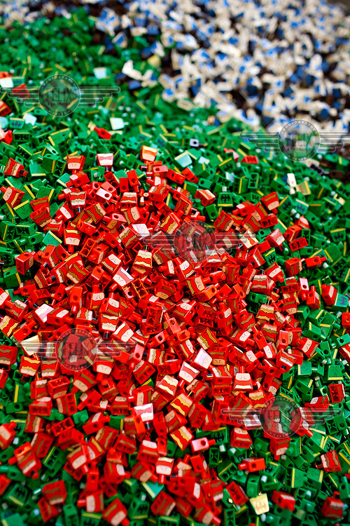 A pile of red and green bricks in the LEGO factory.