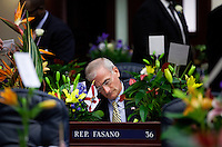 TALLAHASSEE, FLA. 3/5/13-OPENING030513CH-Rep. Mike Fasano, R-New Port Richey, is nearly covered by the flowers commemorating the start of the 2013 session on his desk as he catches up on paperwork prior to the start of the House session, Tuesday at the Capitol in Tallahassee, Fla...COLIN HACKLEY PHOTO