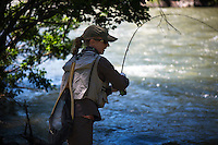 A woman fights a rainbow trout on the Gallatin River near Big Sky, Montana.