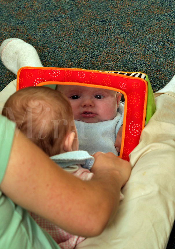 Infant looking at self in mirror.