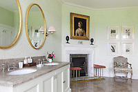 A luxurious pale green bathroom with damask wallpaper and polished marble floors