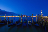 Gondolas moored at jetty against the background of San Giorgio Maggiore and the Grand Canal, Venice, italy.