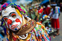 A dancer (danzante), masked as a clown, performs in the religious parade within the Corpus Christi festival in Pujilí, Ecuador, 10 June 2012. Every year in June, thousands of people gather in a small town of Pujili, high in the Andes, to celebrate the Catholic feast of Corpus Christi. Introduced originally during the Spanish conquest of South America, this celebration merges Catholic rituals of Holy Communion with the traditional Andean harvest and sun festivities (Inti, the Inca sun god). Women dancers perform wearing brightly colored costumes while men dancers wear chest ornaments and heavy elaborate headdresses adorned with mirrors, jewelry, or natural items (shells). Being a dancer in the Corpus Christi ceremonial parade (El Danzante) is considered an honour and a privilege by the indigenous people in Ecuador.