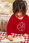 2 year old toddler girl playing with wooden puzzle toy vertical