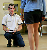 Physiotherapist assessing a patient in an NHS hospital..