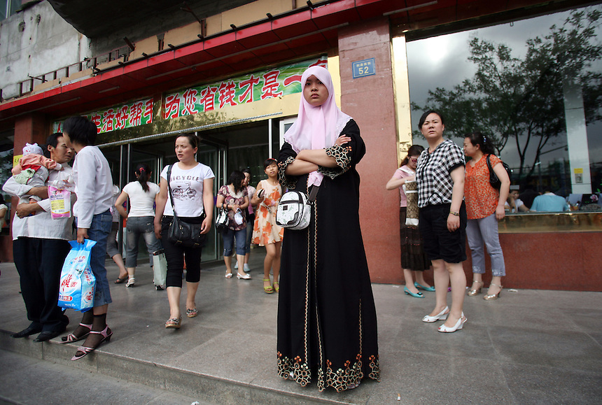 A Muslim Hui woman in front of a department store in Wuzhong in Ningxia China.