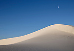 The moon sets over a large dune at White Sands National Monument, New Mexico