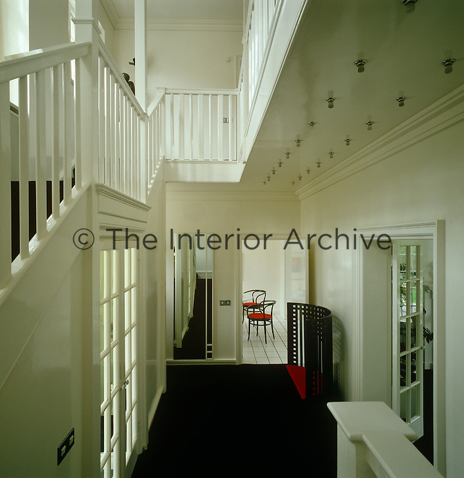 The red of the seat provides the only splash of colour in this black and white entrance hall
