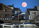 The Sturgeon moon rises over beach front homes in Well, Maine on August 14, 2019. Photo by Christopher Evans