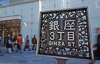 Shoppers pass a sign in the upmarket Ginza shopping district, Tokyo, Japan..