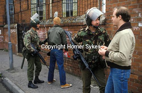 Belfast Ireland 1980s, British soldiers stop and search on  Islandbawn street of Belfast.