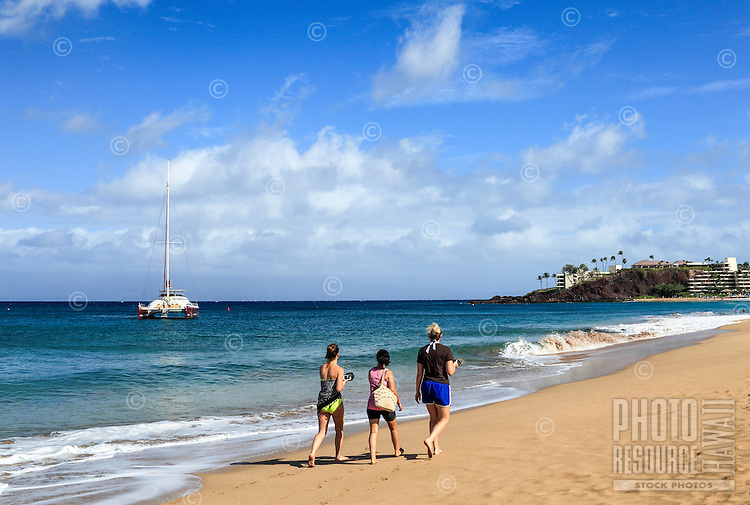 Women walk toward Black Rock at Ka'anapali Beach, Maui.