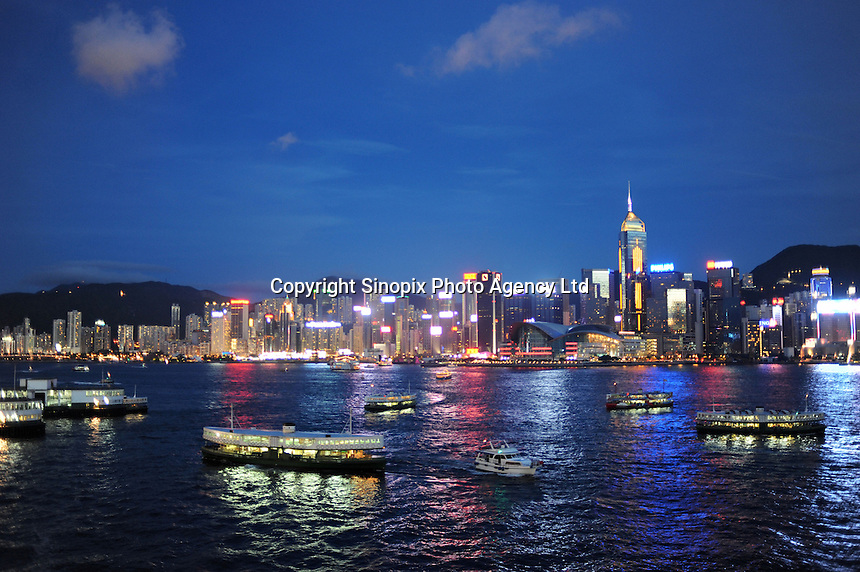 The Star Ferry and other boats in Hong Kong's Victoria harbour with the glittering Hong Kong Island skyline...