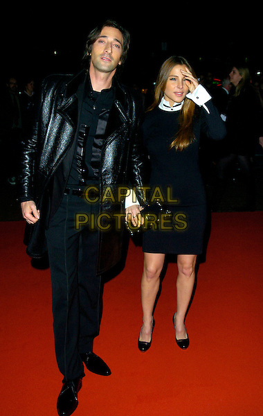 """ADRIEN BRODY & ELSA PATAKY.""""The Darjeeling Limited""""  BFI London Film Festival closing gala, Odeon Leicester Square, London, England..November 1st, 2007.LFF full length adrian black leather jacket dress clutch bag purse hand couple white cuffs  .CAP/CAN.©Can Nguyen/Capital Pictures"""