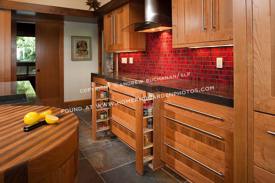 Custom cherry cabinetry, bright red tile, and a slate tile floor complement one another in this striking kitchen. Pull-out shelves on either side of the stove provide efficient storage for spices.