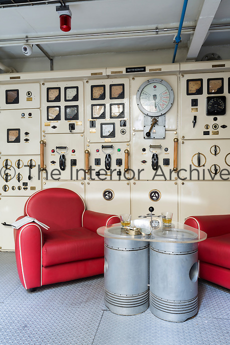 The original Russian electrical control panel in the engine room, now purely decorative, is the centrepiece of an unusual seating area furnished with red leather mid-century armchairs