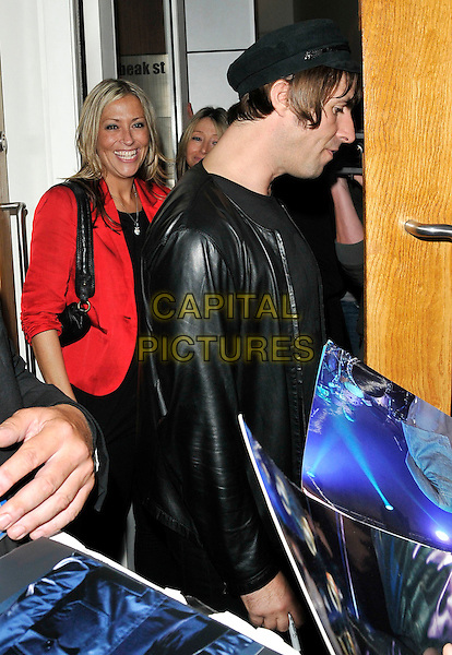 NICOLE APPLETON & LIAM GALLAGHER.At the Pretty Green Pop-Up store launch reception, Pretty Green, Carnaby Street, London, England, UK, July 29th 2010..half length black hat cap leather jacket red t-shirt side profile married couple husband wife smiling .CAP/CAN.©Can Nguyen/Capital Pictures.