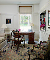Dolores Halpern's study is a feminine and light room with painted panelling and a tapestry armchair