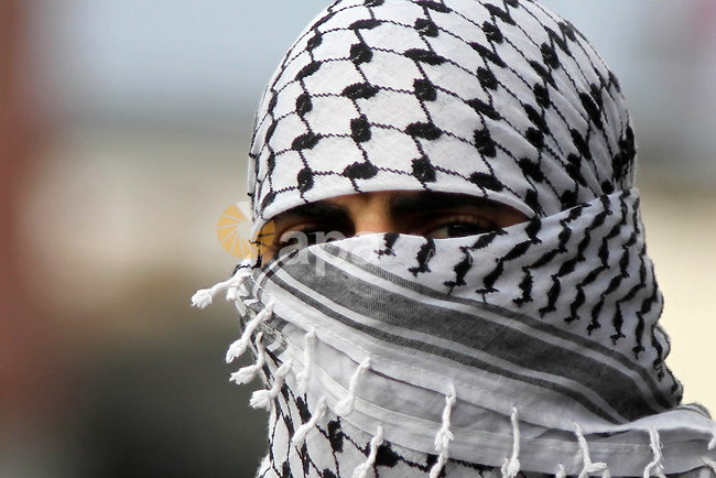 A Palestinian protester looks on during clashes with Israeli security forces following a protest against Israeli restrictions to Al-Aqsa Mosque in Jerusalem, at the Qalandia checkpoint near the West Bank city of Ramallah, November 14, 2014. Israel eased age restrictions for Friday prayers at Jerusalem's flashpoint Al-Aqsa mosque for a second straight week, allowing tens of thousands to attend despite high tensions following a wave of violence. Photo by Shadi Hatem