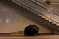 A Homeless man using an umbrella to add to his shelter in an underground arcade in Hamamatsu station, Hamamatsu, Shizuoka, Japan Sunday, March 22nd 2009