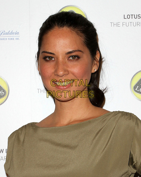 OLIVIA MUNN .U.S. Launch Event for New Lotus Carst held at A Private Residence, Los Angeles, CA, USA, .12th November 2010..portrait headshot smiling hair up  green silk satin khaki .CAP/ADM/KB.©Kevan Brooks/AdMedia/Capital Pictures.