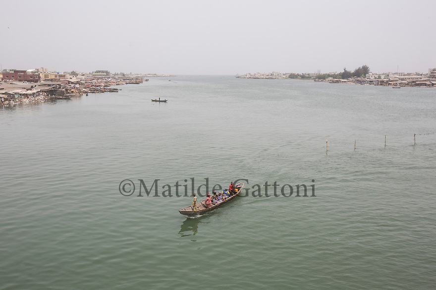 Benin - Cotonou - A passenger boat crosses the lagoon. Urbanization and migration have turned the coastal areas of West Africa into the economic hubs of the region. Most of the main cities, infrastructures and economic assets of the region are located along the coast.<br /> Sea level rise and coastal erosion are affecting more than 7,000 km of West African coast, from Mauritania all the way to Cameroon. Sea levels along the West African coast are expected to rise faster than the global average.