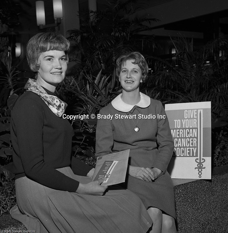 Pittsburgh PA: Two women receiving information from the American Cancer Society Benefit at the new Allegheny Center Mall on the North Side of Pittsburgh - 1966.  The Daniell Sapp and Boorn agency put on the event to benefit the American Cancer Society and the new Allegheny Center Mall.  The mall recently opened and extra publicity is always a good thing.  Daniell Sapp and Boorn which opened in 1962, was active in helping good causes which indirectly promoted their insurance services. During the 1950's and 1960's local corporations and companies were very active in supporting non-profit and charitable organizations.