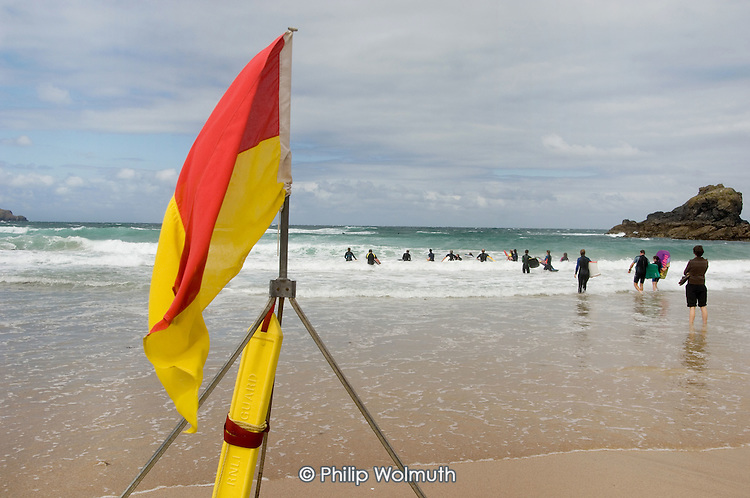 RNLI lifeguard flag warning of dangerous rip tides on a surfing beach at Trevone, North Cornwall.