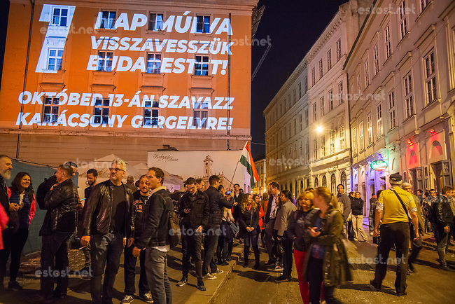 "UNGARN, 12.10.2019, Budapest - V. Bezirk. Kommunalwahlen am 13. Oktober - Aktivisten der vereinten Opposition, angefuehrt von  Oberbuergermeister-Kandidat Gergely Karácsony, nutzen die letzte Ratssitzung am Abend vor der Wahl fuer eine symbolische Besetzung des Rathauses. Projektion draussen: ""Noch ein Tag und wir erobern Budapest zurueck!"" 