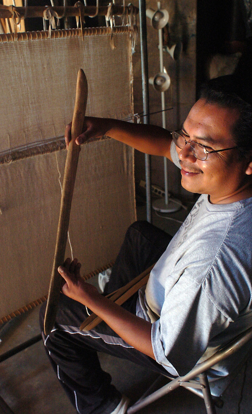 """Hopi weaver James Poley learned on his uncle's upright weaving loom. It was that same loom he inherited as tools are passed down thru the clan only men are weavers and they pass the skill to down to their nephews. Poley hold one tool he believes to be at least 300 years old.  He handles.it real gingerly since he believe if it would fall, it.perhaps might shatter. The batten is known as a """"sukua"""" in Hopi."""