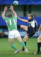 Scotland's scrum half Ross Samson gets this kick away under pressure from Irish winger Paddy Brophy during the Division A clash in the U19 World Championship at Ravenhill.