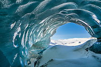 Cross country skier in the distant hillside viewed from inside a glacier ice cave in the Alaska Range mountains, Interior, Alaska.