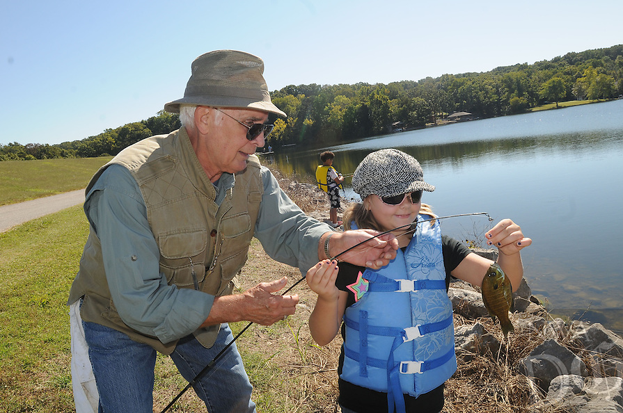 NWA Democrat-Gazette/FLIP PUTTHOFF <br /> Lloyd Okeson with the Bella Vista Fly Tyers helps Eve Reagan catch a sunfish Sept. 30 2016 at Lake Windsor. Members of the fishing group helped students from R.E. Baker Elementary in Bentonville with their fishing during a nature education day at the lake.