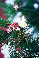 Detail of a papier mache mushroom decoration and small lit candle on the Christmas tree