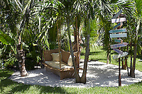 In a corner of the garden a rattan sofa has been positioned under some palm trees as a shady spot for sipping cocktails