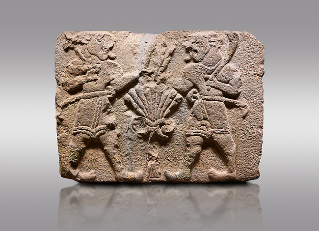 Aslantepe Hittite relief sculpted orthostat stone panel of Lion Men. Limestone, 1399-1301 BC. Anatolian Civilisations Museum, Ankara, Turkey.<br /> <br /> There are two lion-men with a sword at their waists on both sides of the tree of life. The figure on the right holds a sickle in his left hand resting on his shoulder and a symbol his right hand. The figure on the left carries a double-faced ax in his right hand. <br /> <br /> Against a gray background.