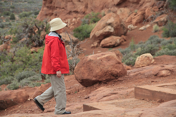 Asian person walking in Arches National Park, Moab, Utah, USA. .  John offers private photo tours in Arches National Park and throughout Utah and Colorado. Year-round.