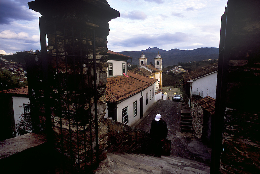 A local hikes the cobblestone hills of Ouro Preto (circumflex over the e in Preto), Brazil. At rear, Nossa Senhora da Merces do Baixo (circumflex over the secoond e in Merces), or the Lower Church of Our Lady of Merces -- there is aonther on a higher hill -- in Ouro Preto (circumflex over the e in Preto), Brazil. Brazil's interior state of Minas Gerais, once a colonial mining capitol for the Portuguese crown, has changed little in appearance since the 18th century. With the help of laws to preserve its baroque architecture, the state's sky is scraped at every turn by 250-year-old church steeples, and lined with cobblestones. (Kevin Moloney for the New York Times)